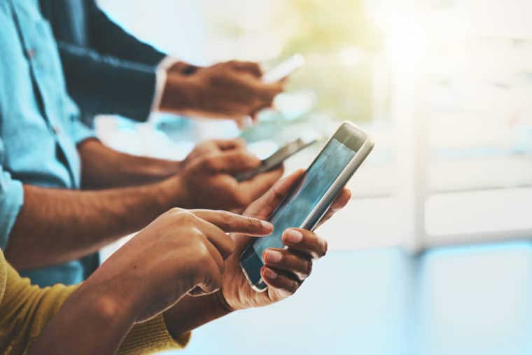 A cropped shot of three sets of hands hold mobile phones all in a row and demonstrates the many options for mobile friendly website design!