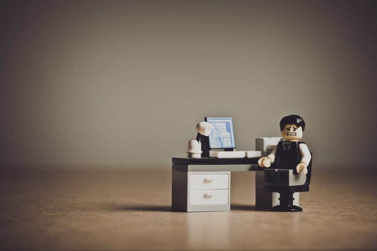 A lego business character sits at a desk with a computer and a frazzled expression on its face. What to do when your website goes down.