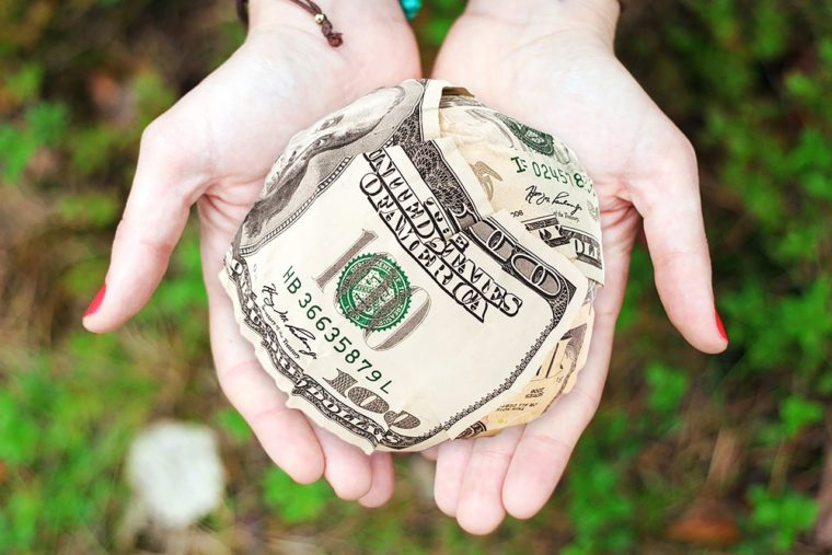 Fundraising featured image shows white hands with red fingernail polish holding a balled up bundle of money.