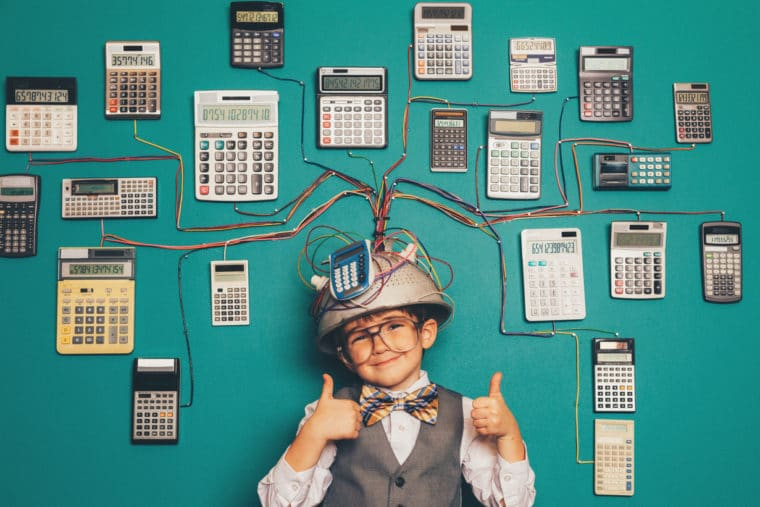 A young boy dressed as a stereotypical nerd is giving two thumbs up and wearing a pretend helmet and calculator invention that we're sure helps him process google analytics for nonprofits!