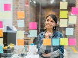 A smiling woman stands and reviews a wall of colorful post-it notes, examining her plan for social media for nonprofits.