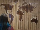 Cornershop founder Lesley examines a world map made out of wood with multi-colored city markings.