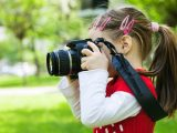 A young girl with a red shirt holds a camera to her eye. Featured image for planning images.