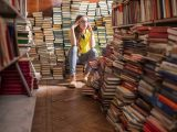 A woman in a yellow shirt sits amidst piles of books and media files and looks like she has a headache.