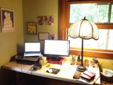 A Cornershop Creative employee's office setup. Desk, laptop on top of printer, second monitor, and old fashioned lamp