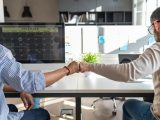Two colleagues share a fist bump to celebrate the work they're doing together. Read this guide to learn more about the top nonprofit consultants for digital fundraising, marketing, and more.