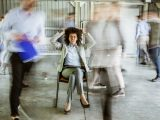 Troubleshooting WordPress websites can be frustrating! A woman sits on a chair, pulling at her hair in frustration while surrounded by blurred, fast-paced images of colleagues.